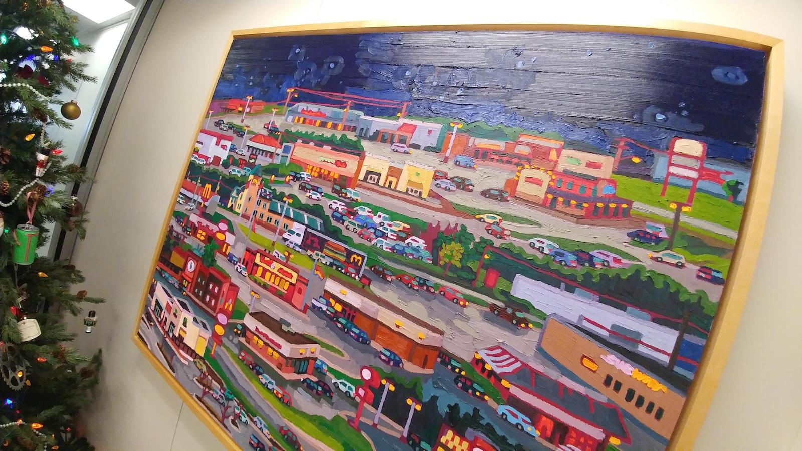 Un tableau d'une toile colorée qui affiche un quartier commercial d'une ville.