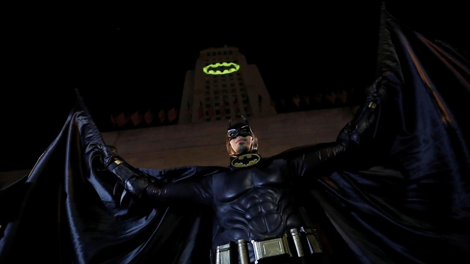 Une personne déguisée en Batman prend la pose devant une projection sur l'hôtel de ville de Los Angeles, en Californie, en hommage à l'acteur Adam West qui incarnait le personnage.