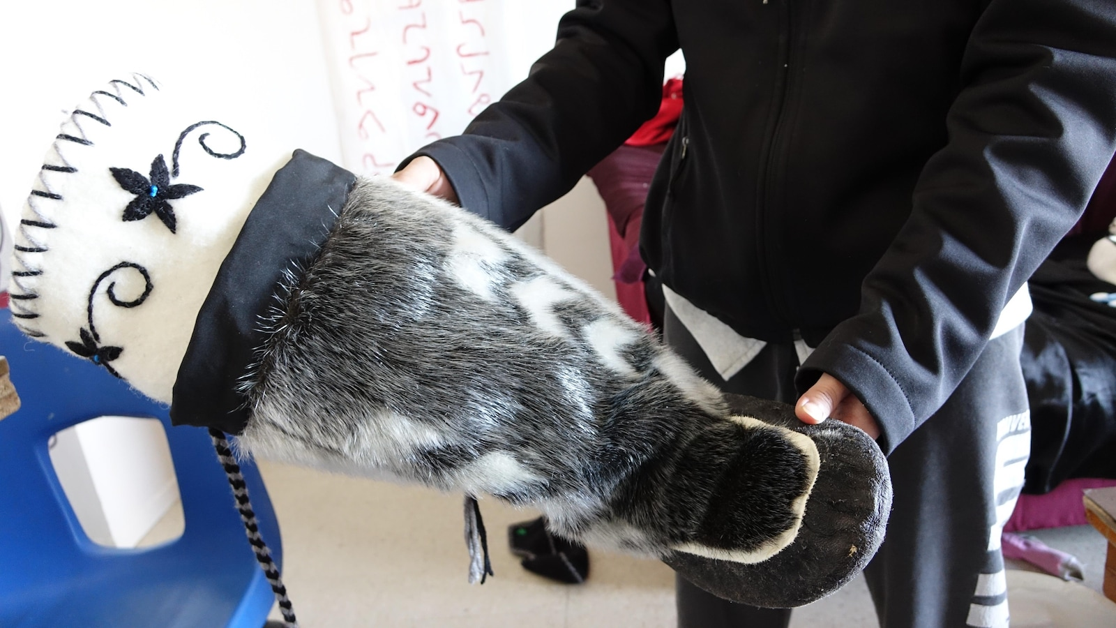 La jeune femme montre une botte en peau de phoque doublée de feutre.