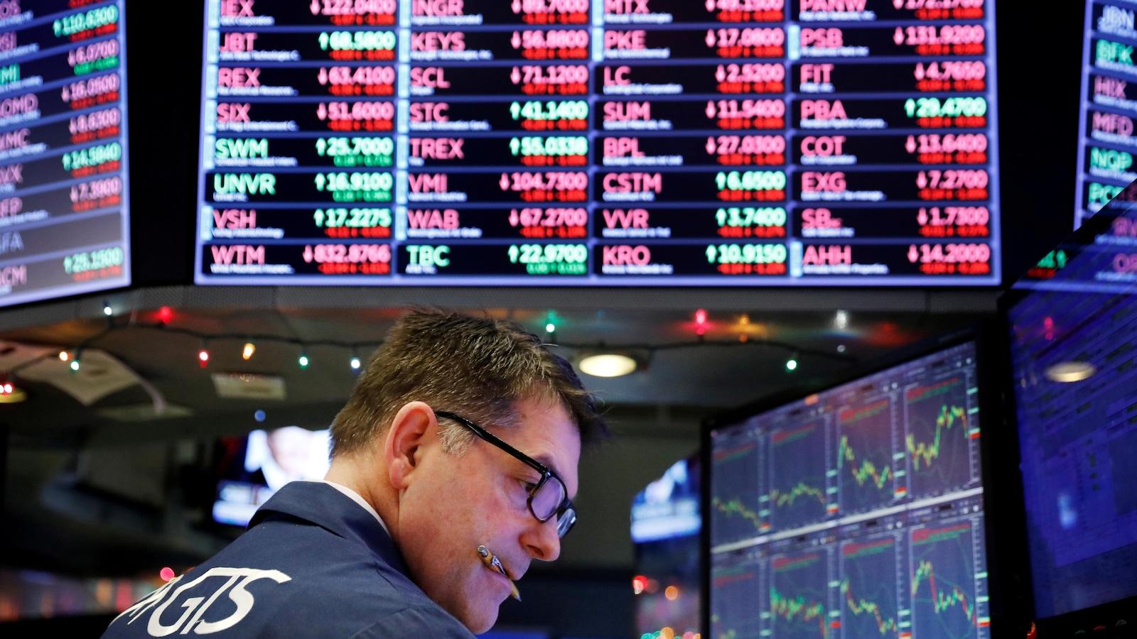 Un homme a un stylo dans la bouche alors qu'il consulte le cours de la bourse sous un énorme écran sur lequel sont affichées diverses actions de compagnies.