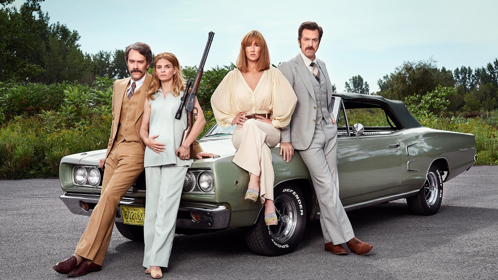 Les acteurs et actrices posent habillés et coiffés comme dans les années 1970 devant une voiture d'époque.