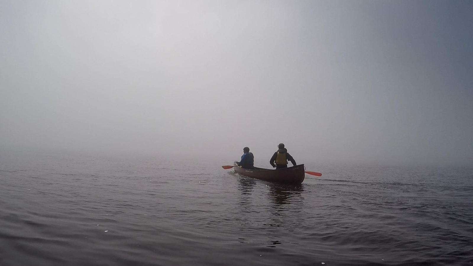 Un canot avec deux personnes, dans la brume