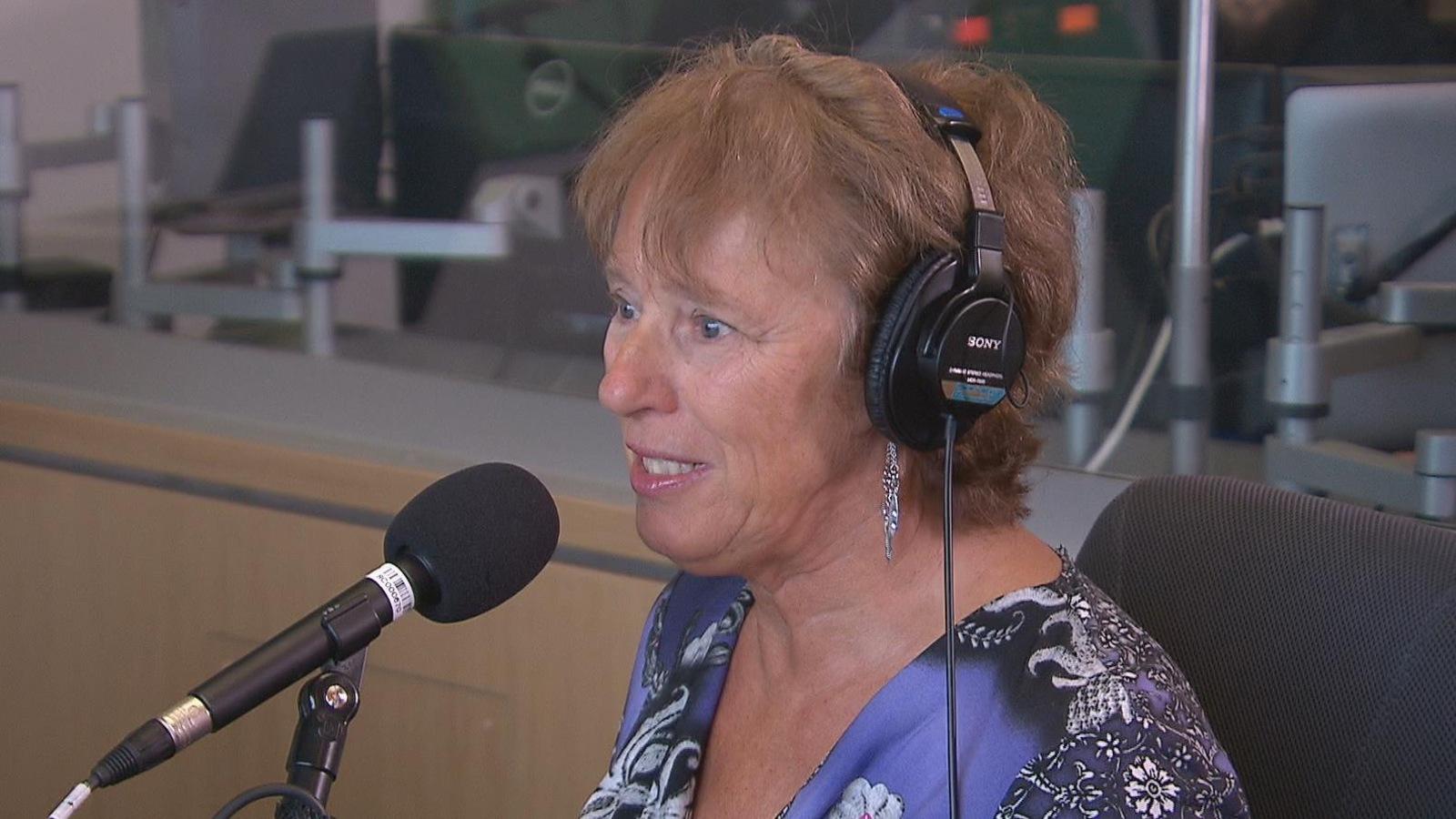 Une femme coiffée d'un casque d'écoute devant un micro