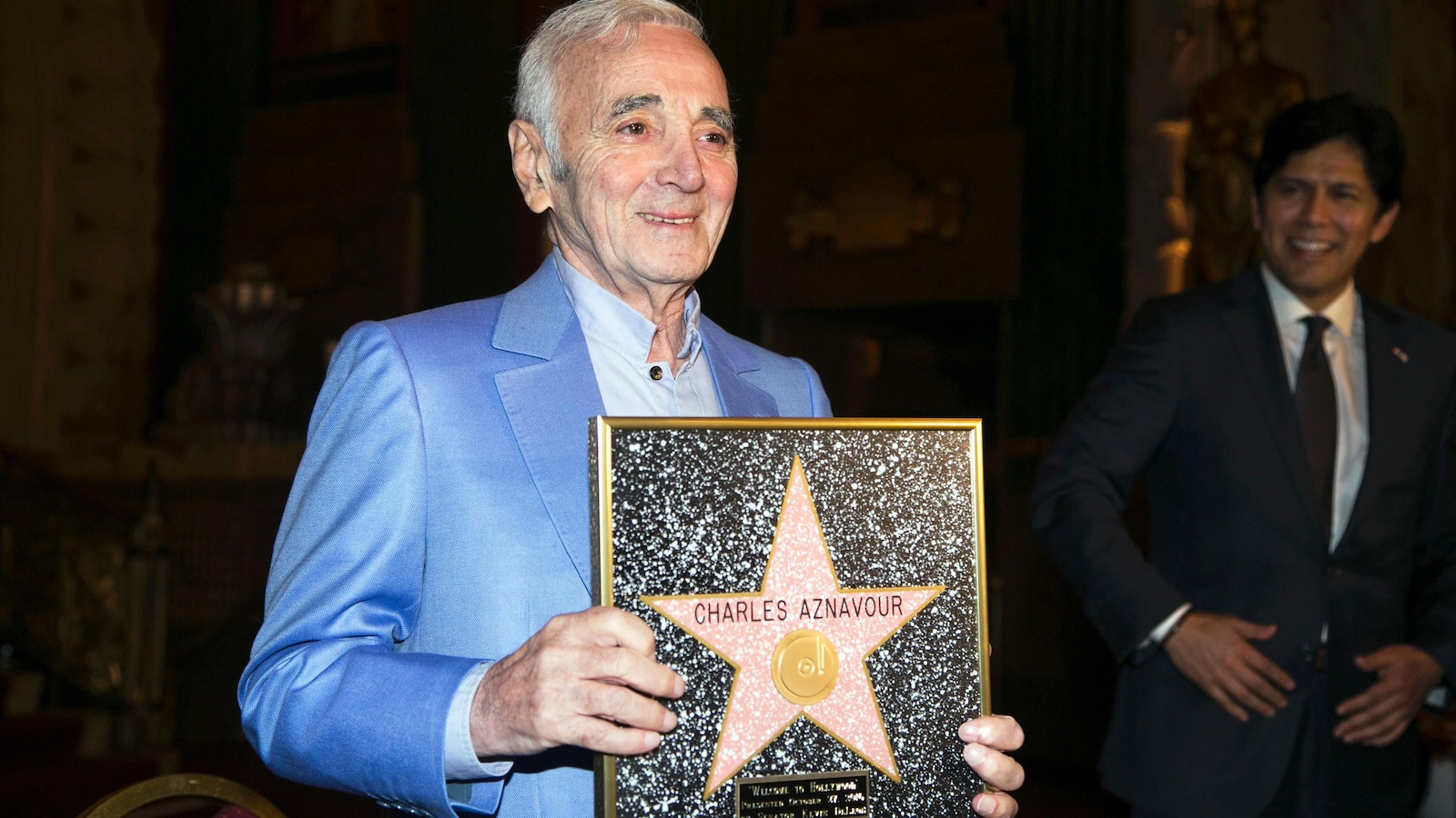 Charles Aznavour tient la plaque honorifique qu'il a reçue au Hollywood Pantages à Hollywood le 27 octobre 2016