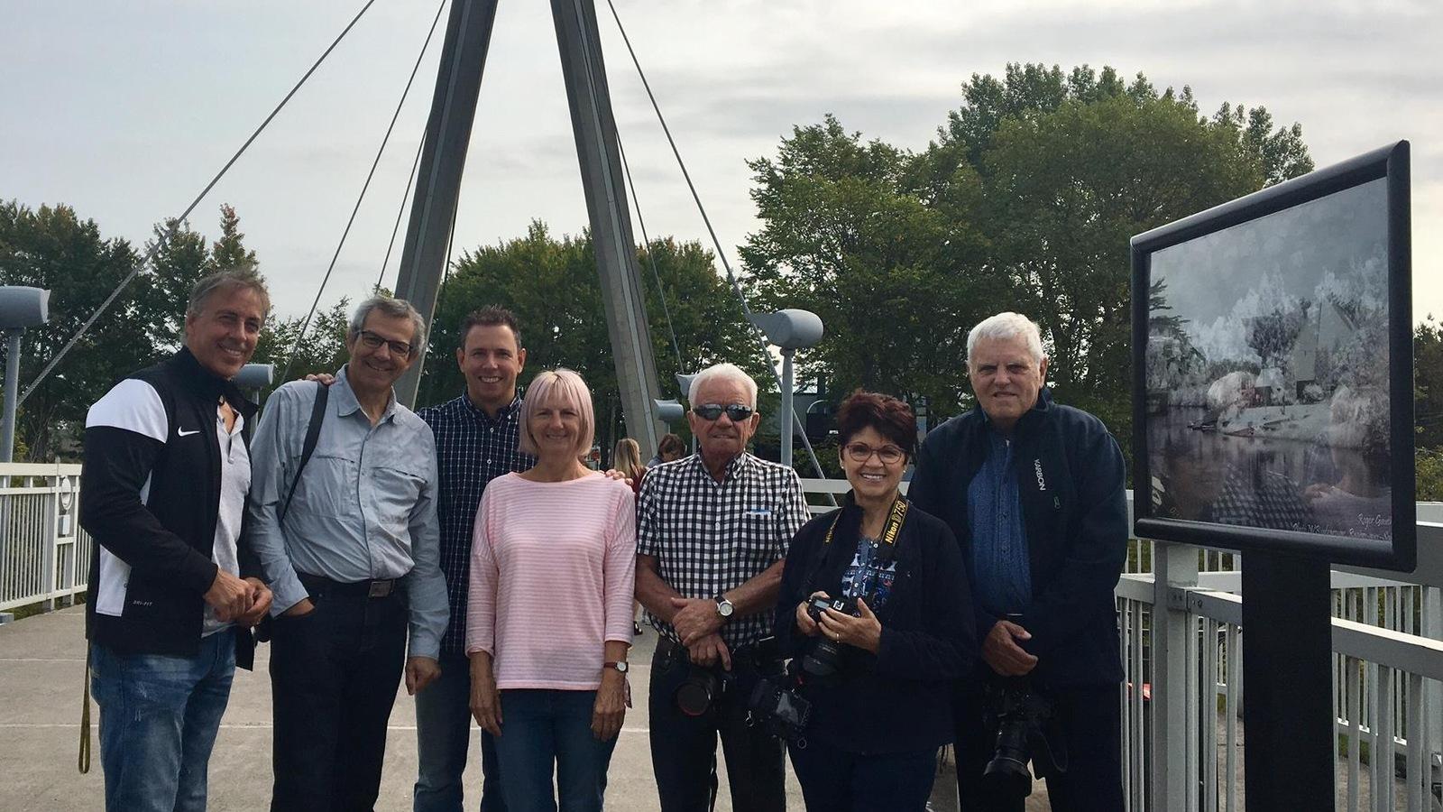 Le conseiller municipal Jonathan Tremblay et des membres du Club photo JAK sur le pont d'aluminium.