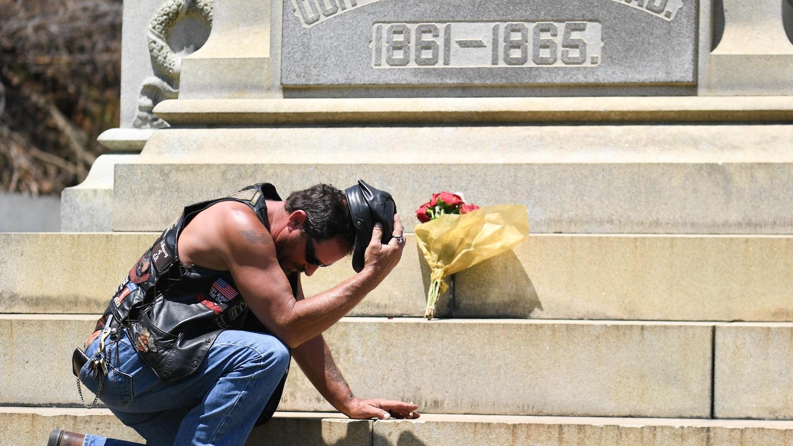 Darrin Powell s'agenouille devant un monument confédéré sur le campus de l'Université de Louisville, qui a depuis été retiré.