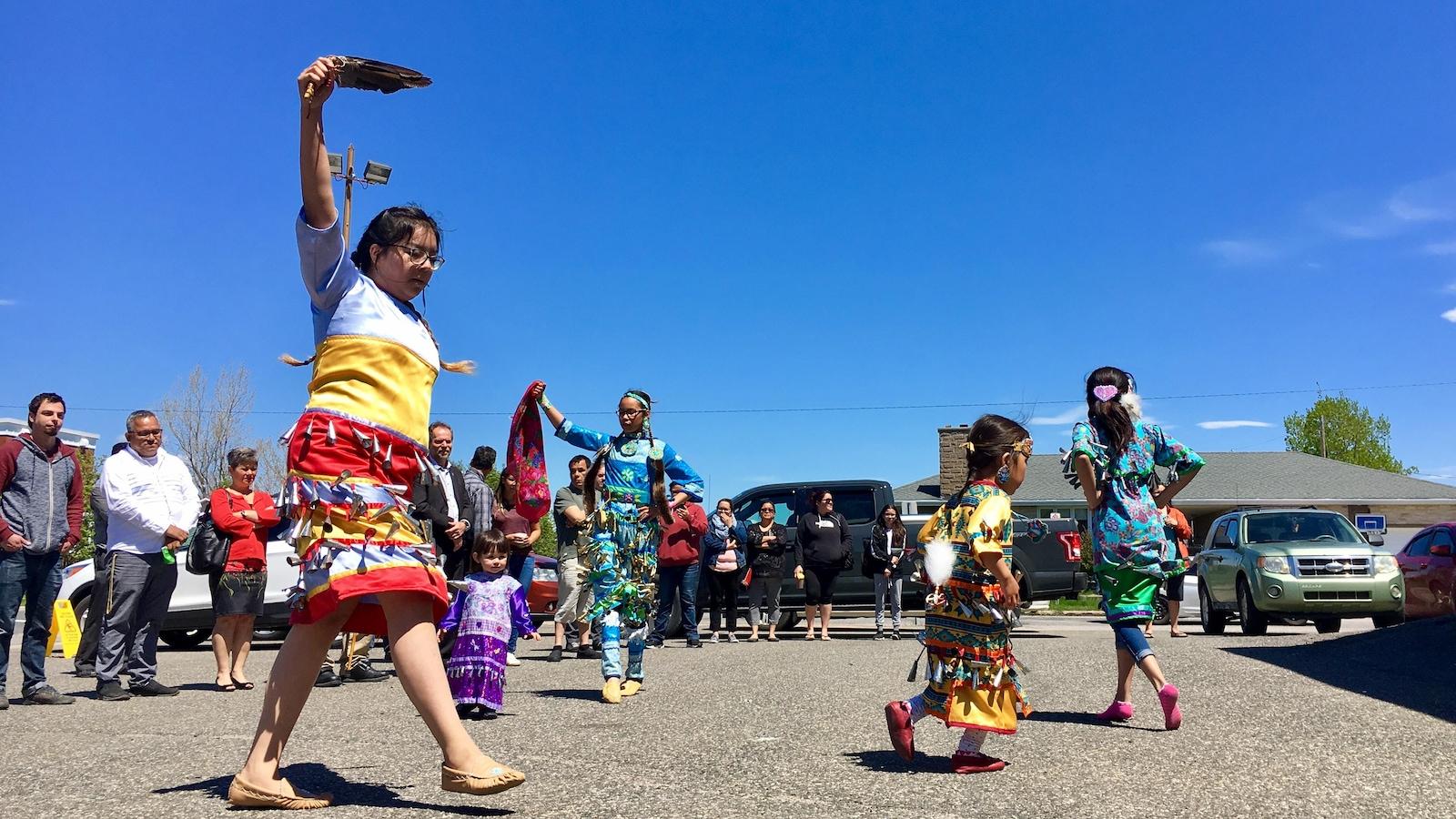 Une jeune femme danse en habit traditionnel autochtone.