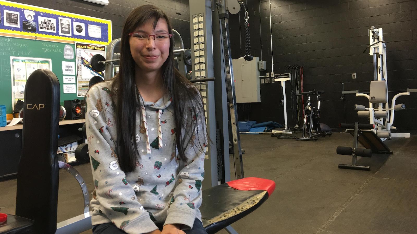 Alaina Sakchekapo, élève en dernière année à l'école secondaire Dennis Franklin Cromarty et membre de l'équipe de lutte, assise sur un banc dans une salle d'entraînement.