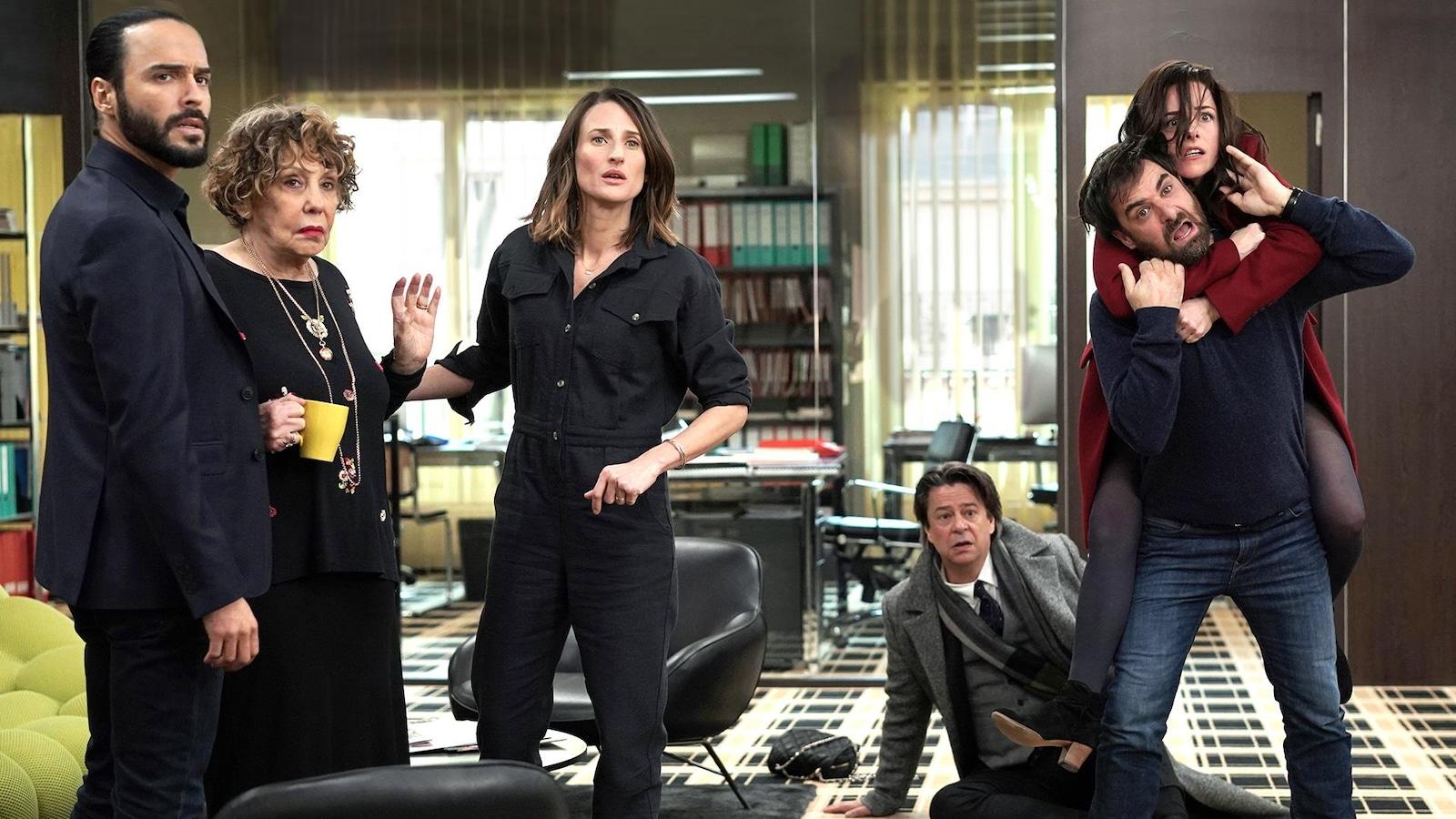 Six personnes sur la photo regardent de manière surprise dans la même direction. L'un est par terre alors qu'une autre est sur les épaules de l'autre.