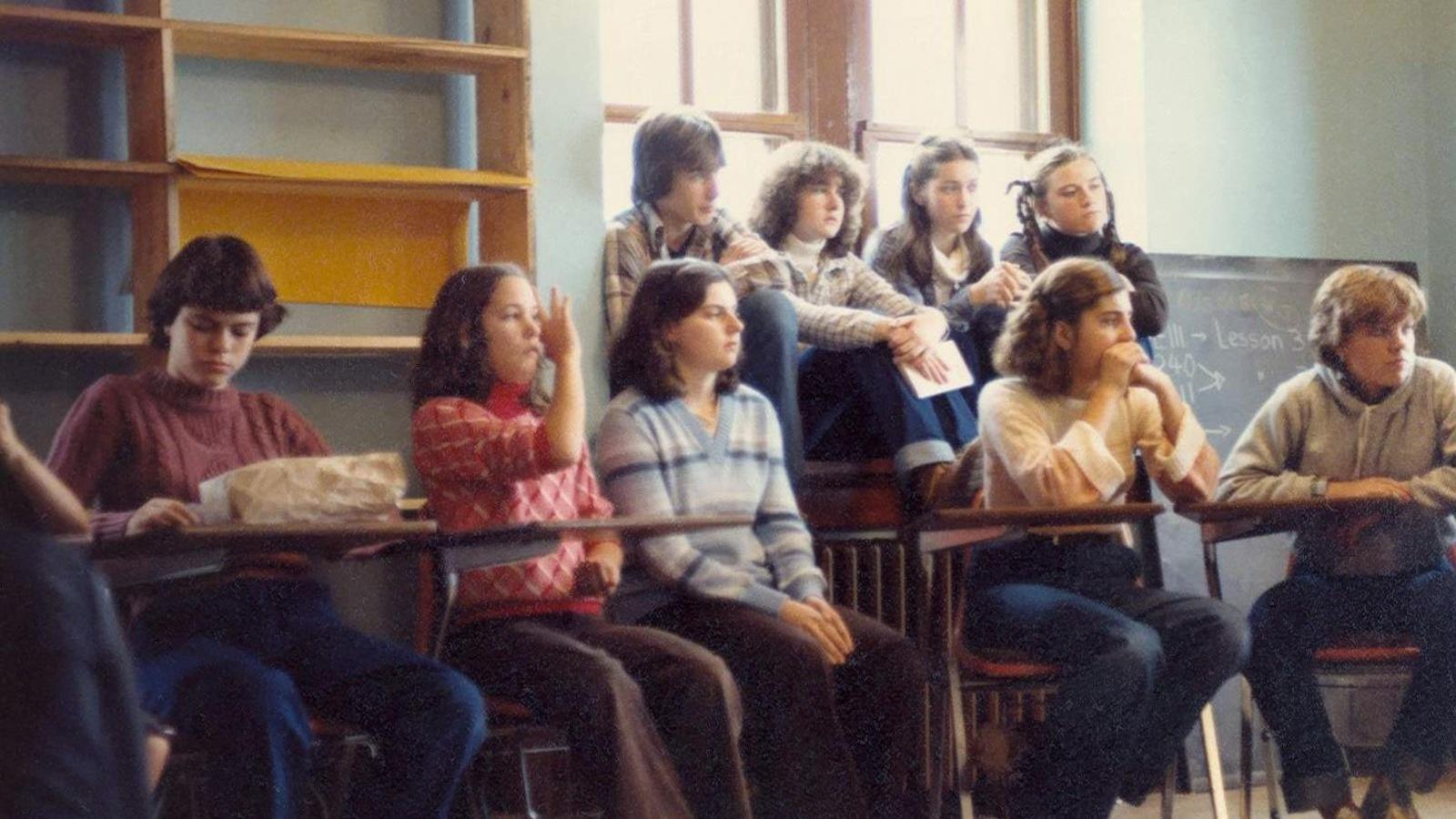 Des élèves sont assis et attentifs en classe.