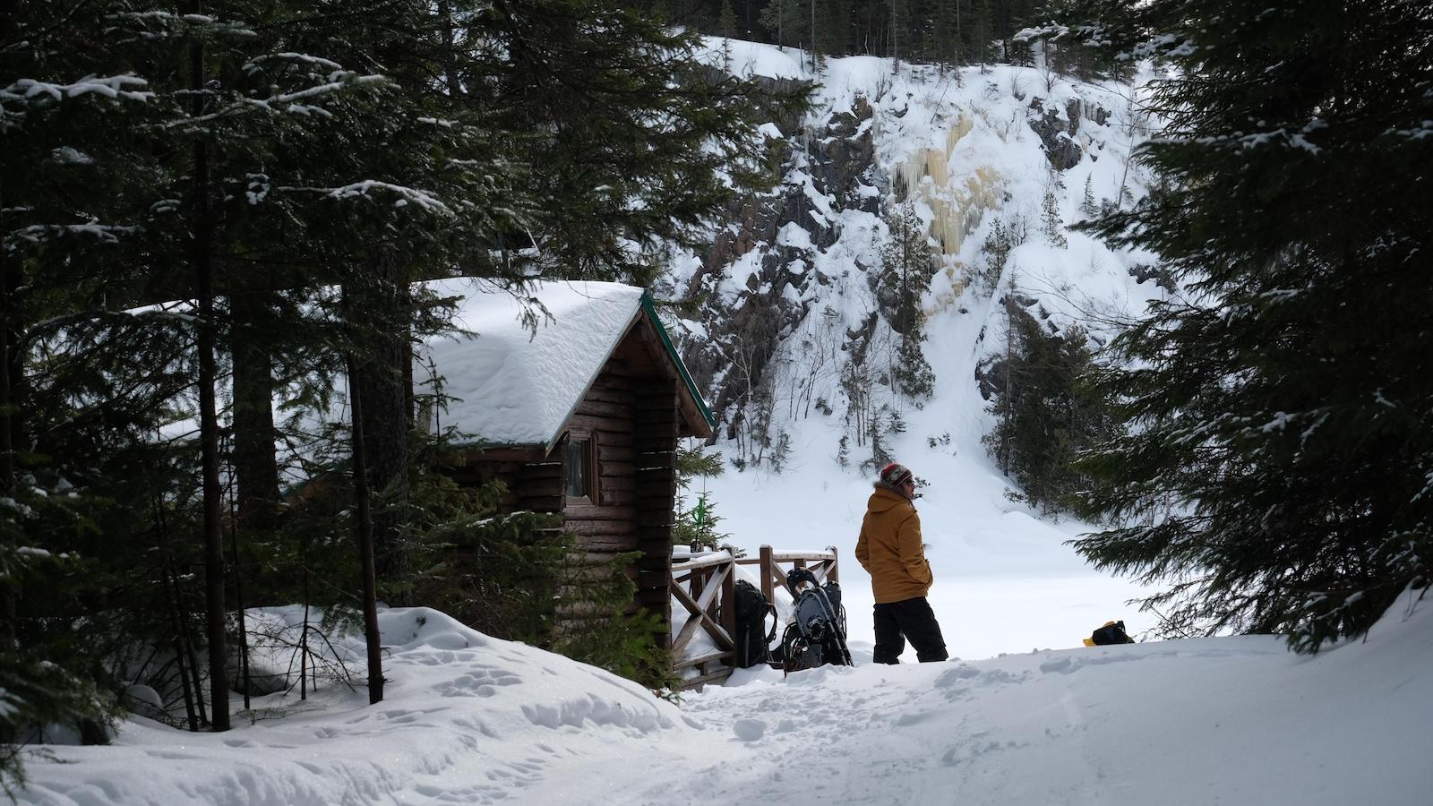 Un homme se tient à proximité d'un chalet. Une paroi glacée est visible à l'arrière-plan.