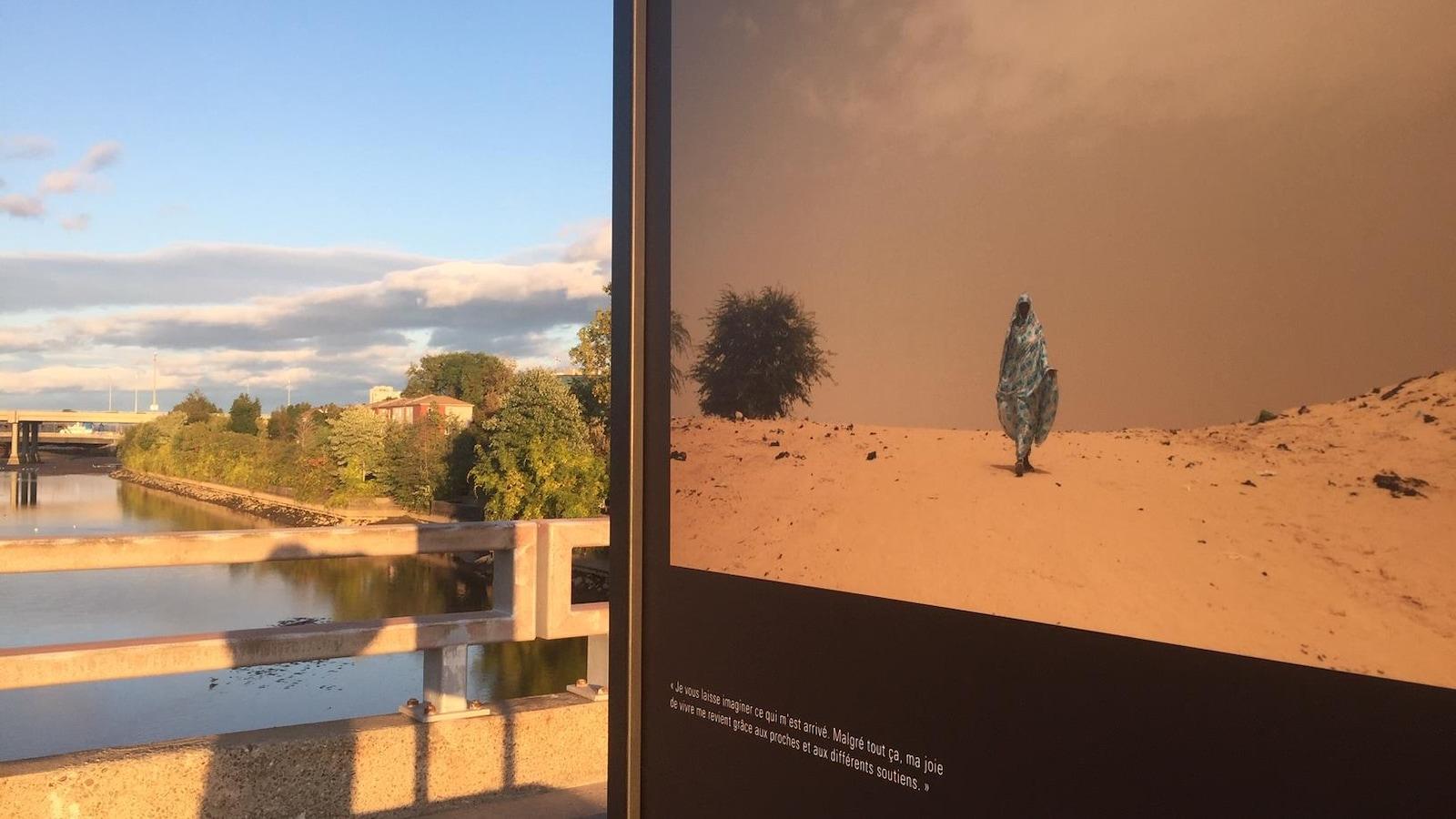 Sur un pont, un panneau montre la photo d'une femme qui marche dans le désert. Une citation de la femme est écrite sous la photo.
