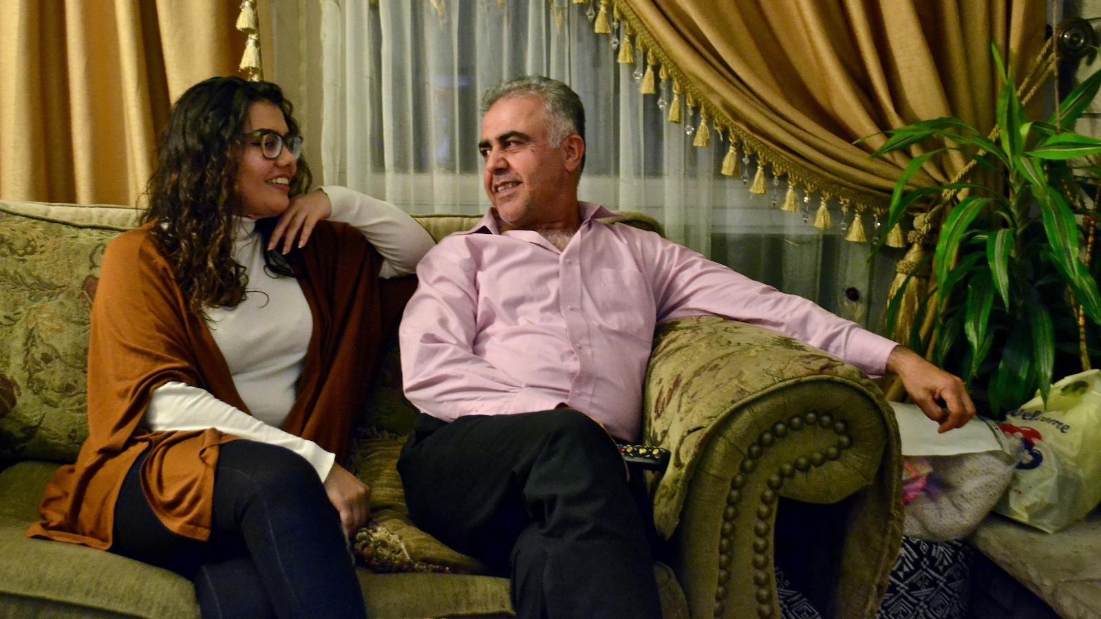 Un père et sa fille assis côte à côte sur un canapé, dans leur salon