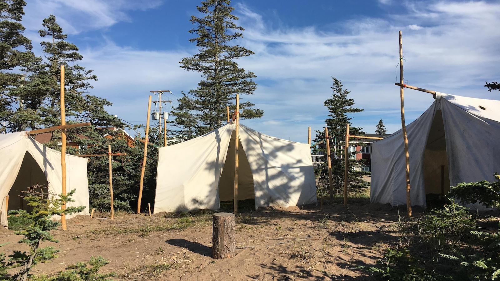 Trois tentes au travers de quelques conifères forment une agora sur le site du festival
