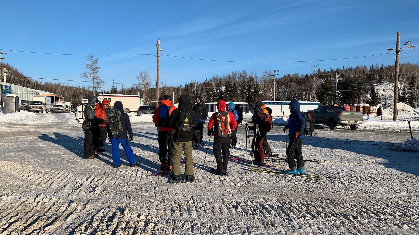 Des skieurs sont rassemblés autour d'un instructeur.