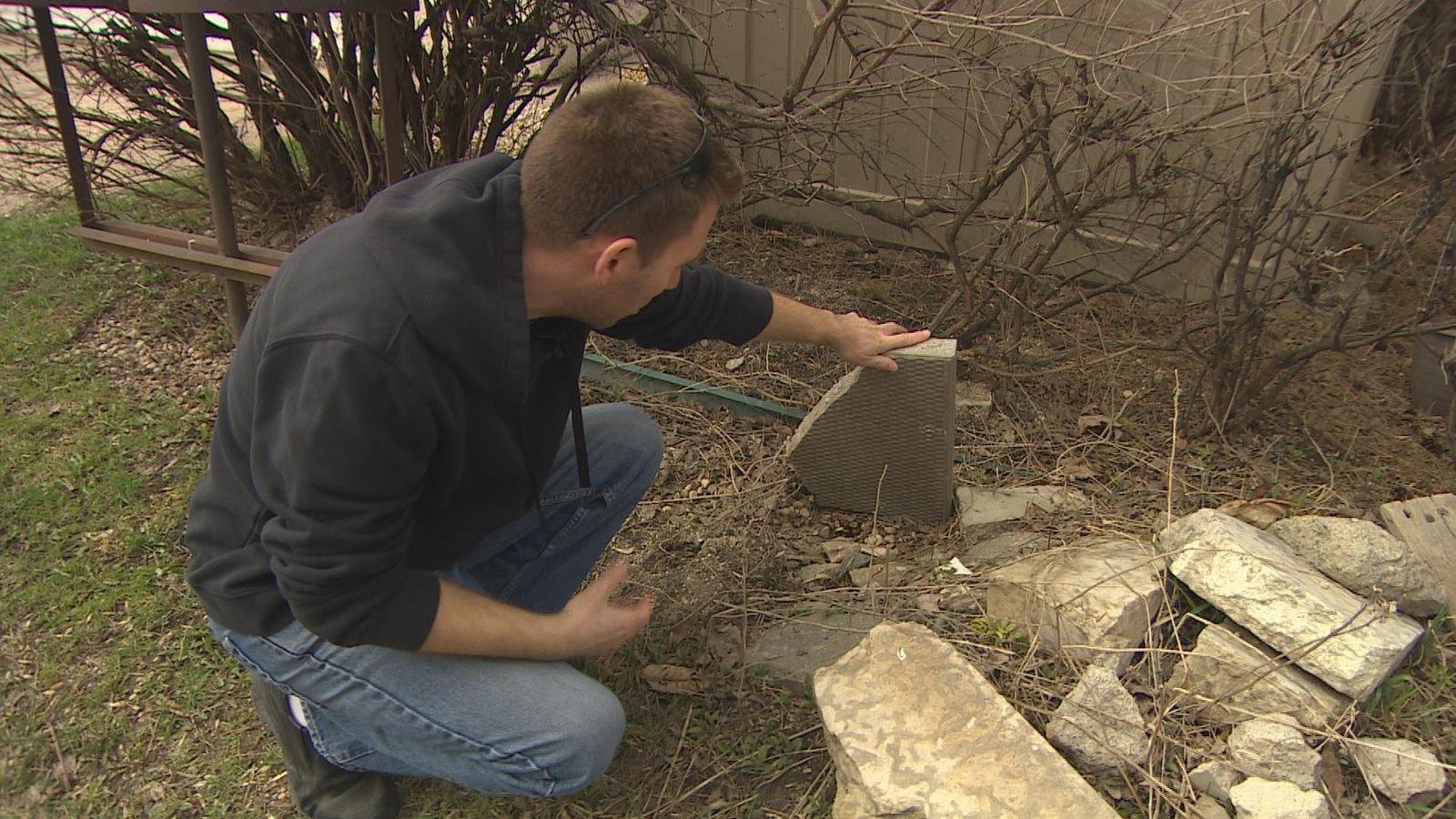 Un homme soulève une pierre dans une ruelle.