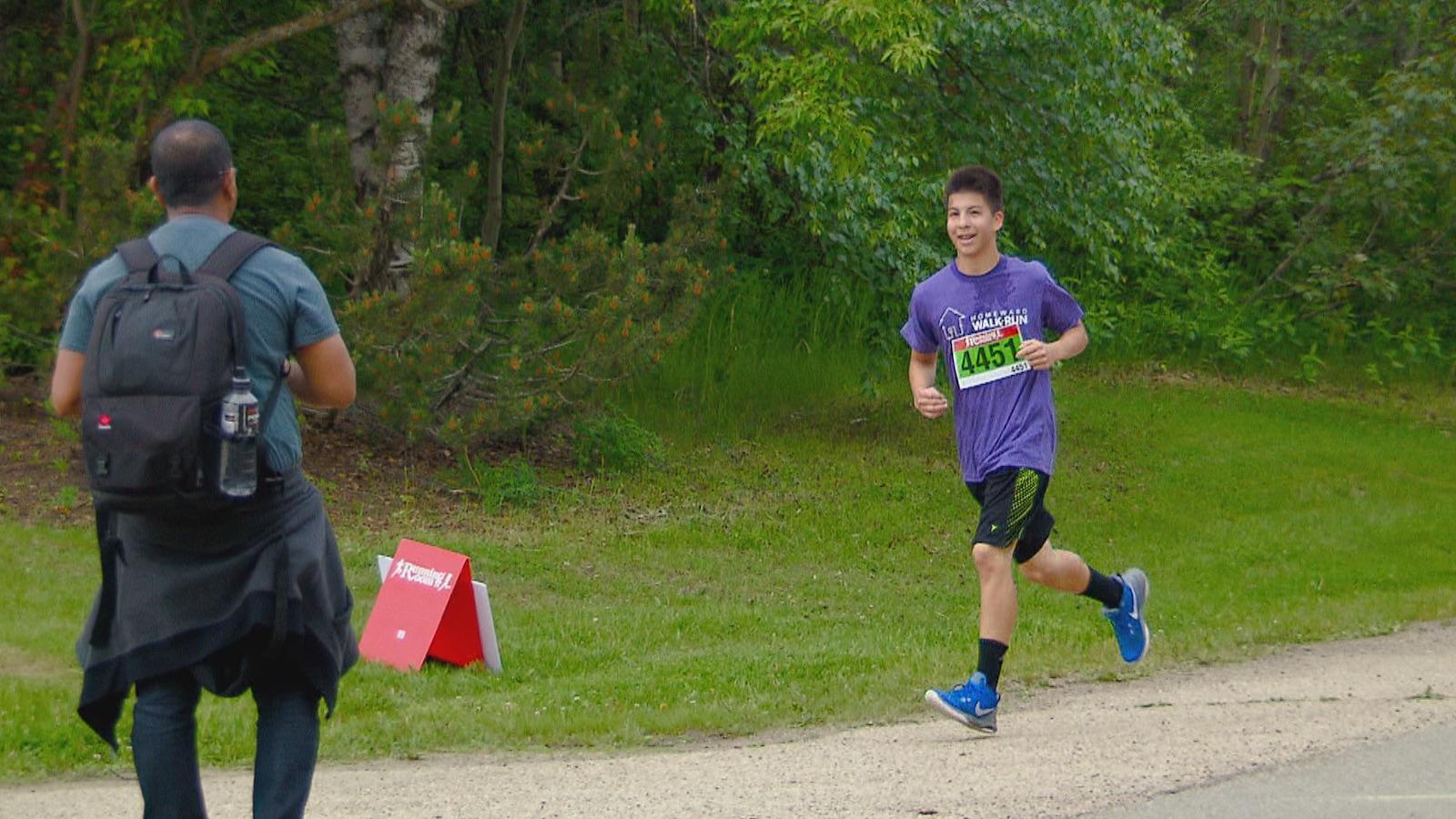 Geovani Robbins, 13 ans, alors qu'il s'apprête à passer le fil d'arrivée d'une course pour sensibiliser le public aux problèmes de l'itinérance à Edmonton.
