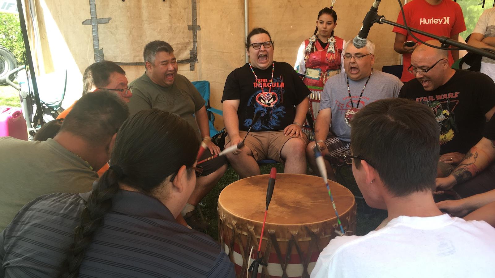Des hommes chantent autour d'un tambour.