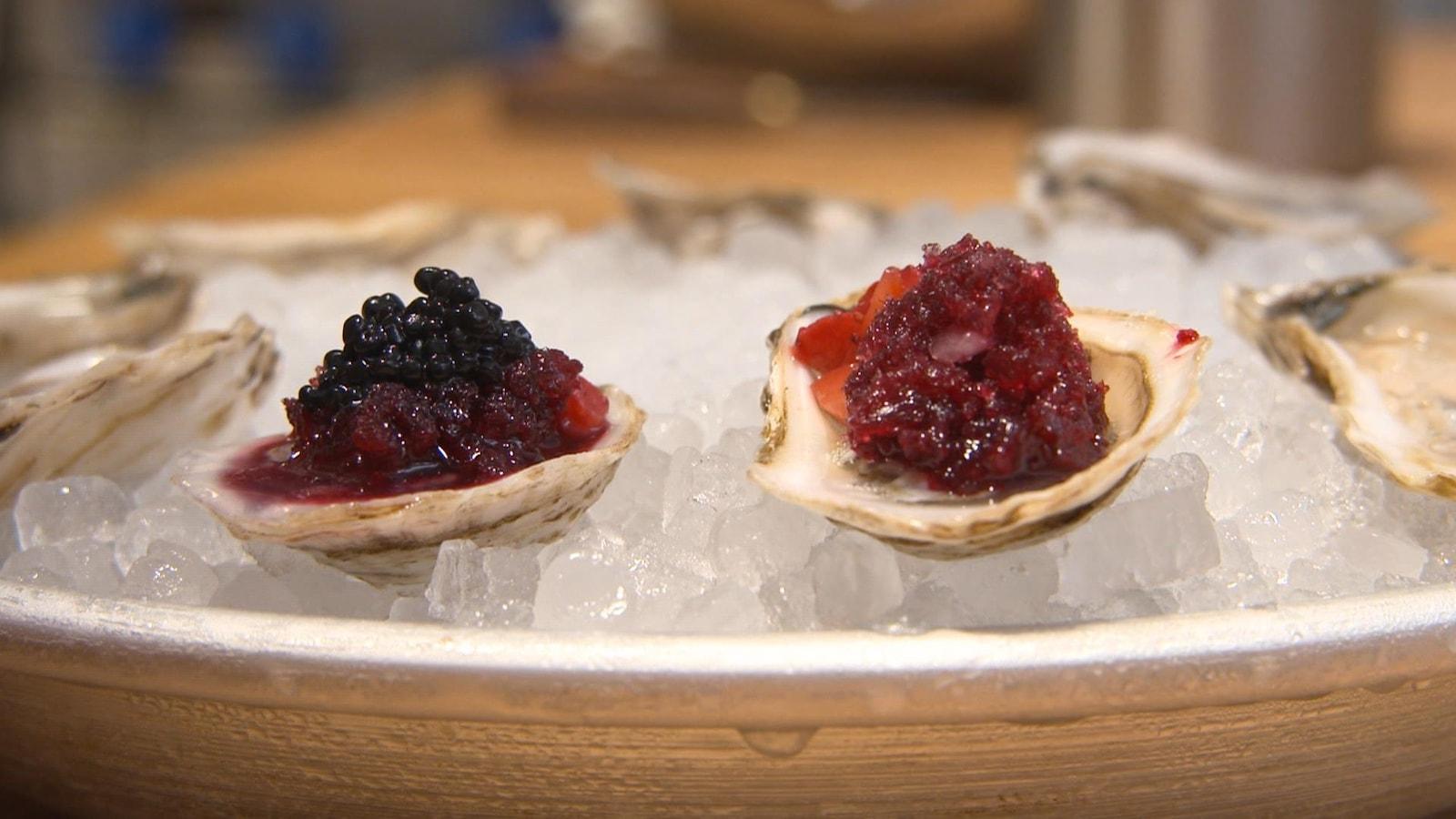 Des huîtres garnies d'un granité d'hibiscus et de caviar, servies sur un lit de glace concassée.