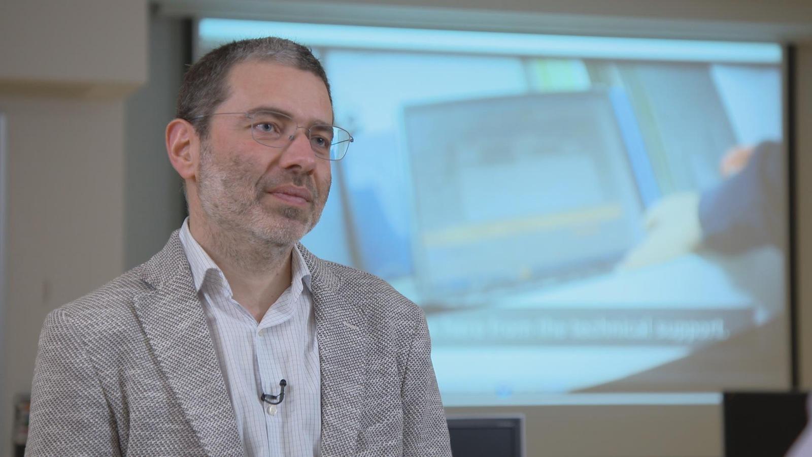 Benoît Dupont devant un écran de télévision.