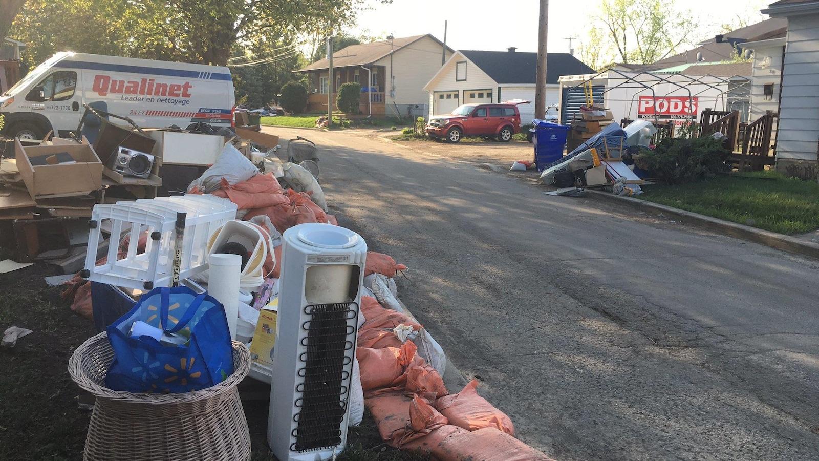 Des distributeurs d'eau des classeurs, des tiroirs de commodes sont empilés à côté de sacs de sables.