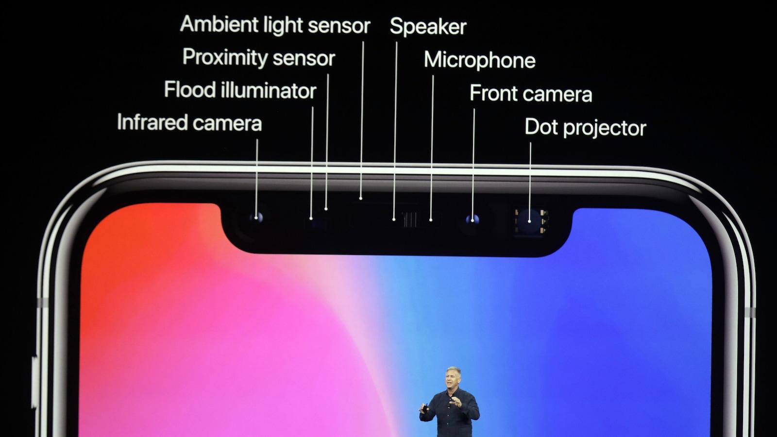 Une photo d'un présentateur sur la scène du Steve Jobs Theater, avec un détail des capteurs du nouvel iPhone X sur un écran géant derrière lui.