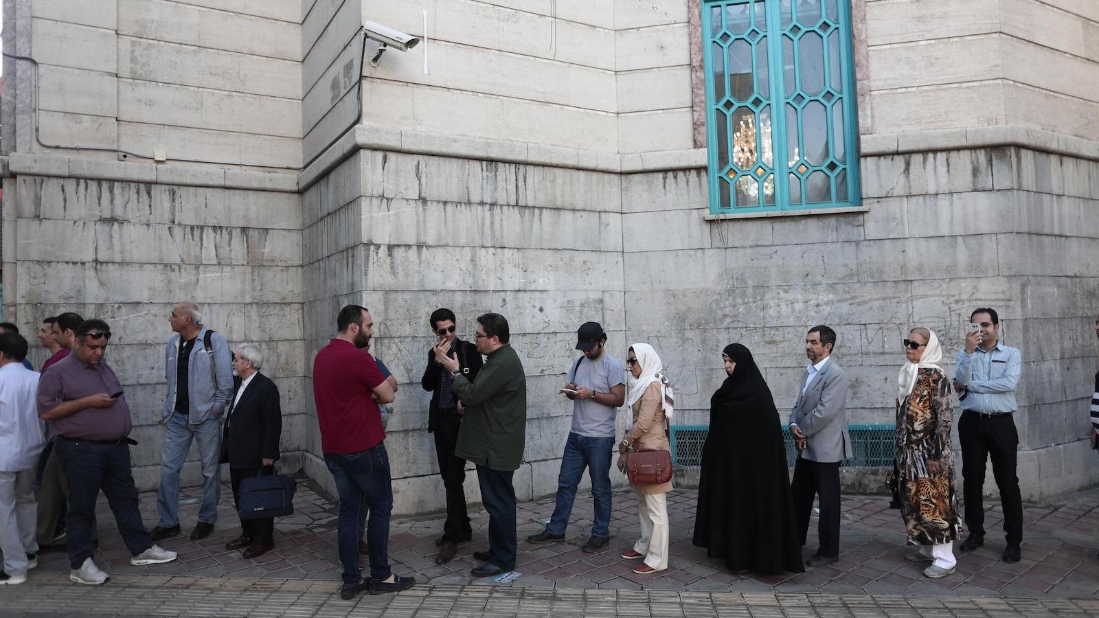 Des hommes et des femmes voilées attendent en file devant un vieil immeuble.