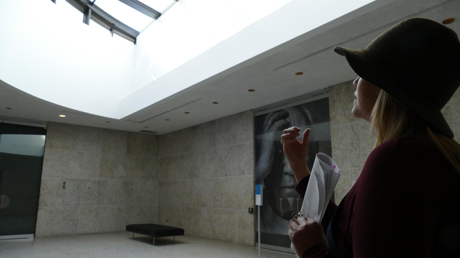 Jaimie Isaac regardant vers le haut le puit de lumière au Musée des beaux-arts de Winnipeg