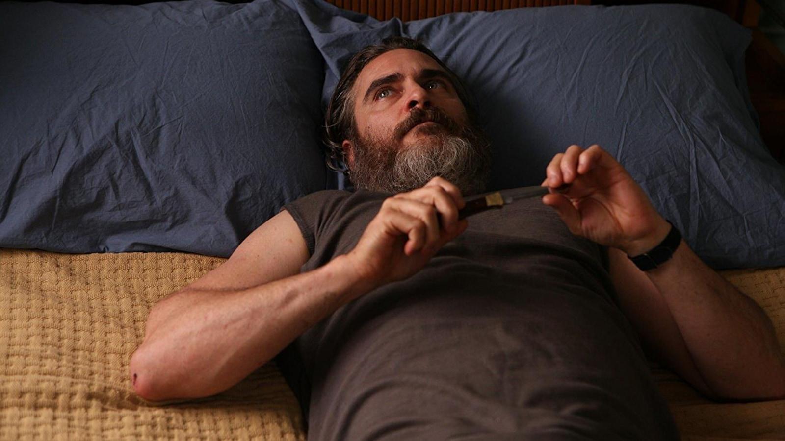 Joaquin Phoenix est allongé sur un lit, avec un couteau dans les mains, dans une scène du film <i>Tu n'as jamais été vraiment là</i>.