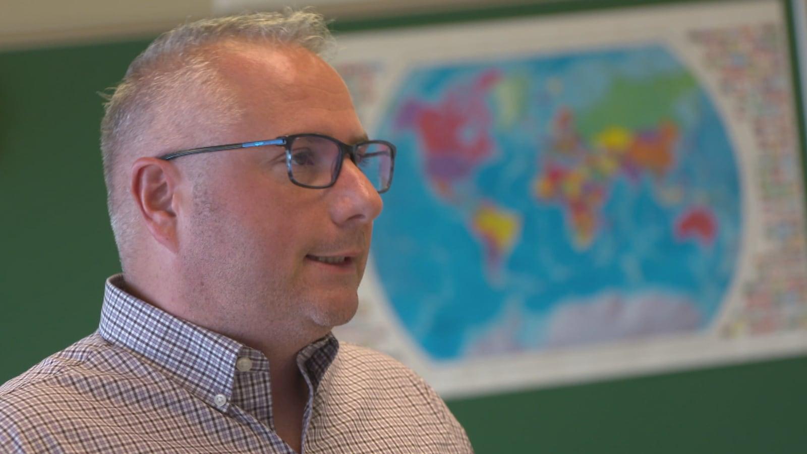 Joël Garneau, une homme avec des lunettes qui porte une chemise