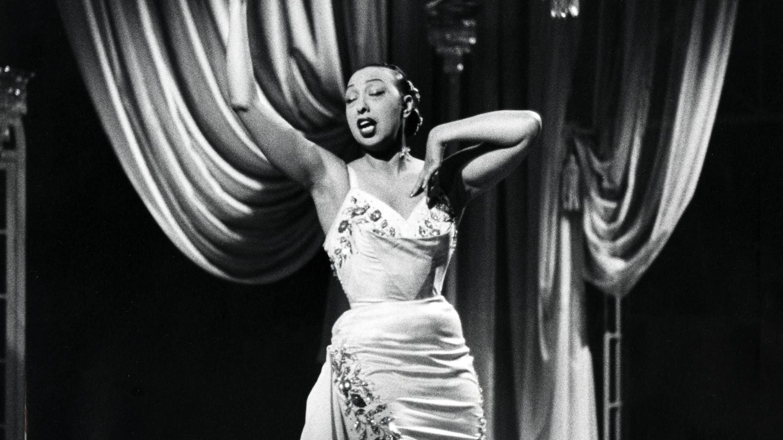 Joséphine Baker chante et gesticule dans un décor de scène.