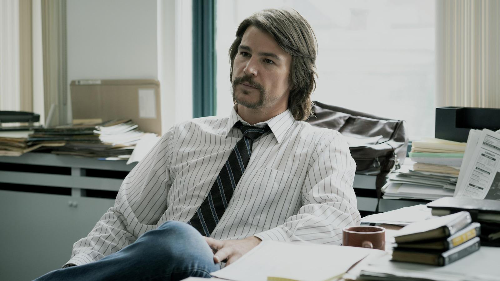 Un homme, avec les cheveux mi-longs, vêtu d'une chemise lignée et d'une cravate bleue, est assis à son bureau.