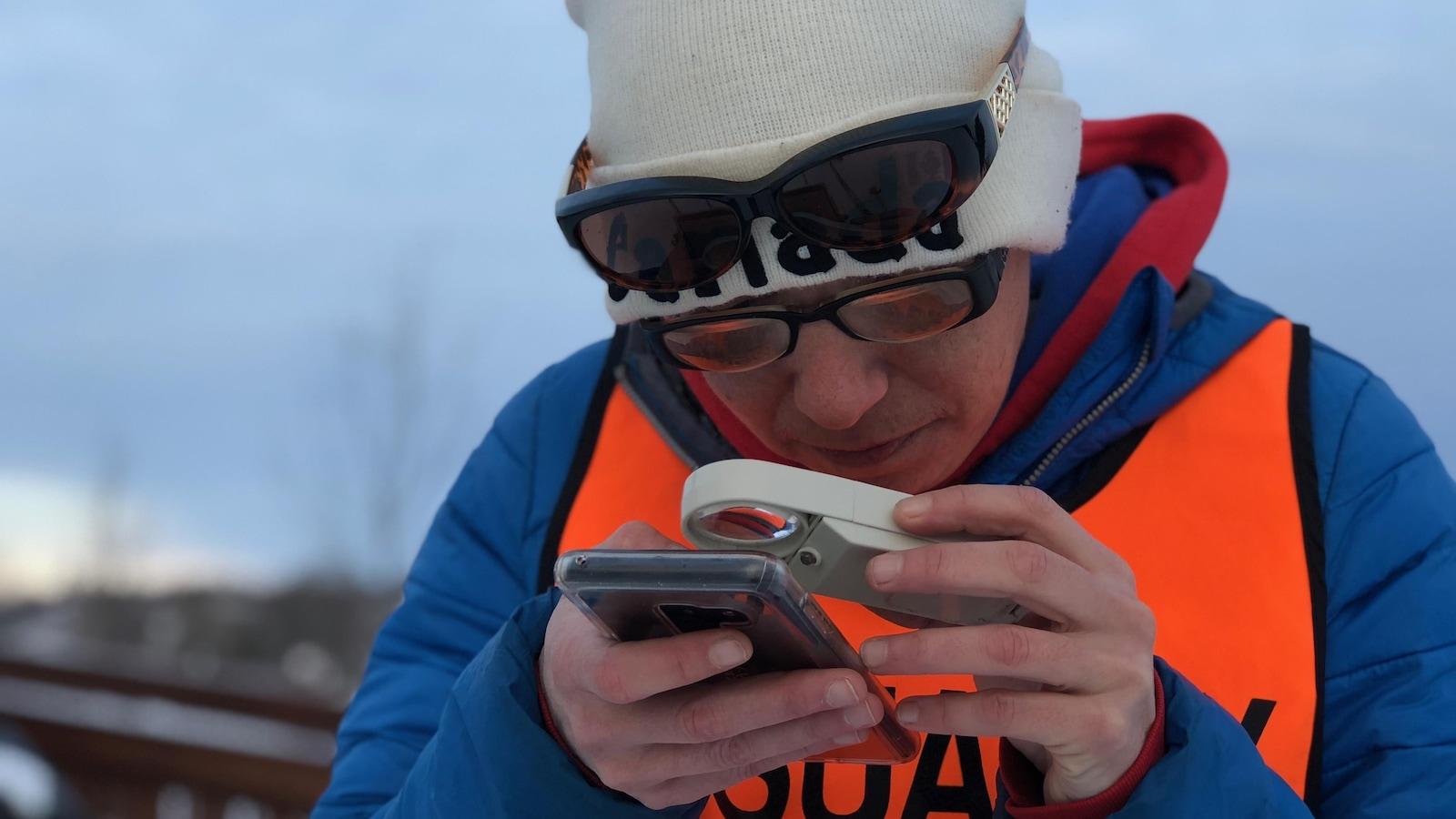 Julie Mayer prend quelques minutes pour observer son application sur le téléphone cellulaire, avant le départ de son entraînement.