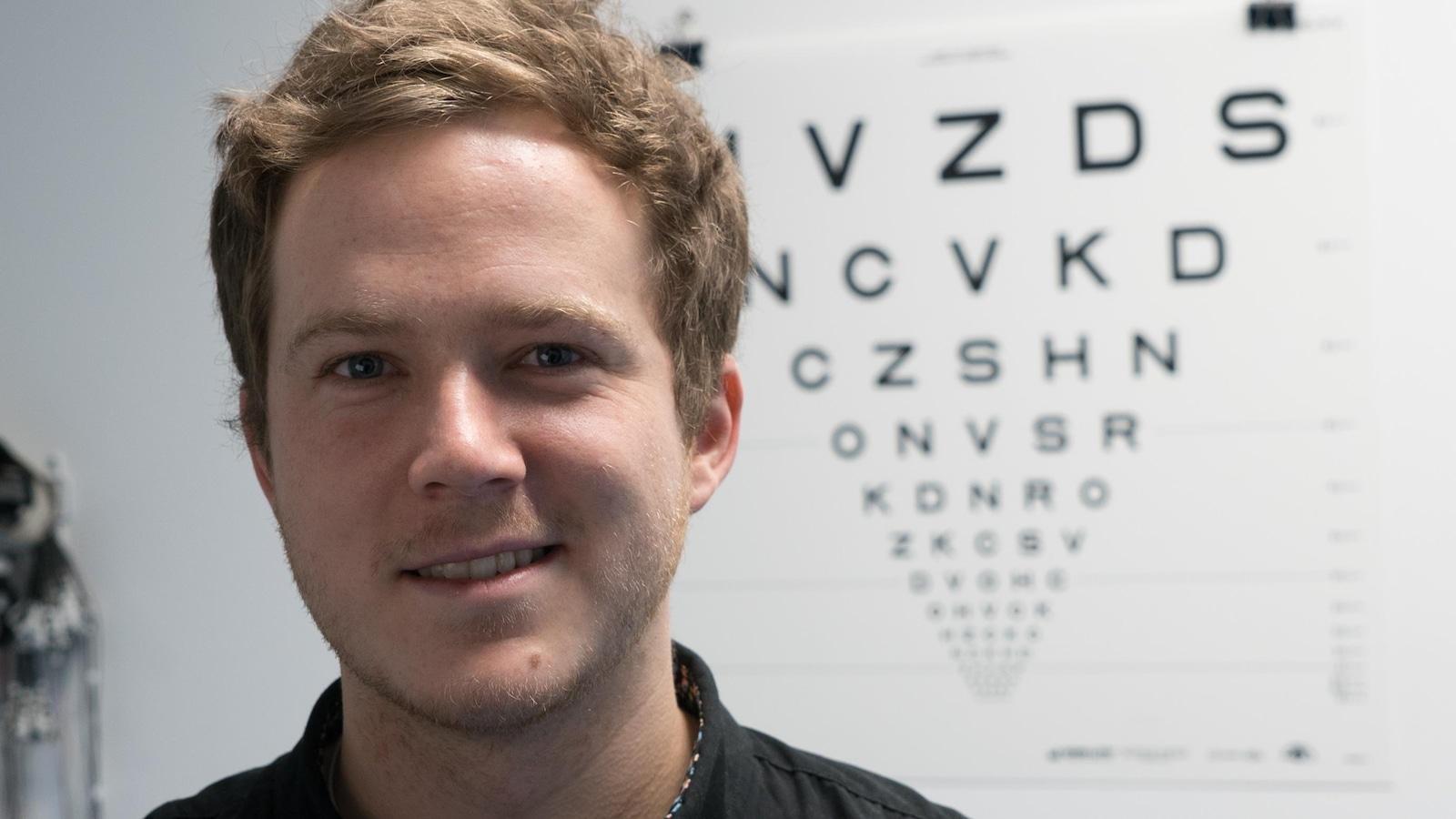 Portrait de Kevin Bastien, souriant, devant un test de vision des lettres de l'alphabet de différentes tailles