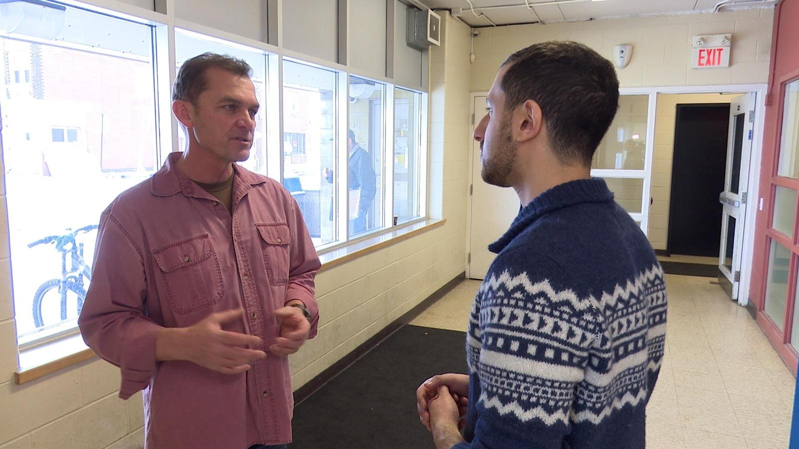 Le directeur parle avec un journaliste devant la caméra.
