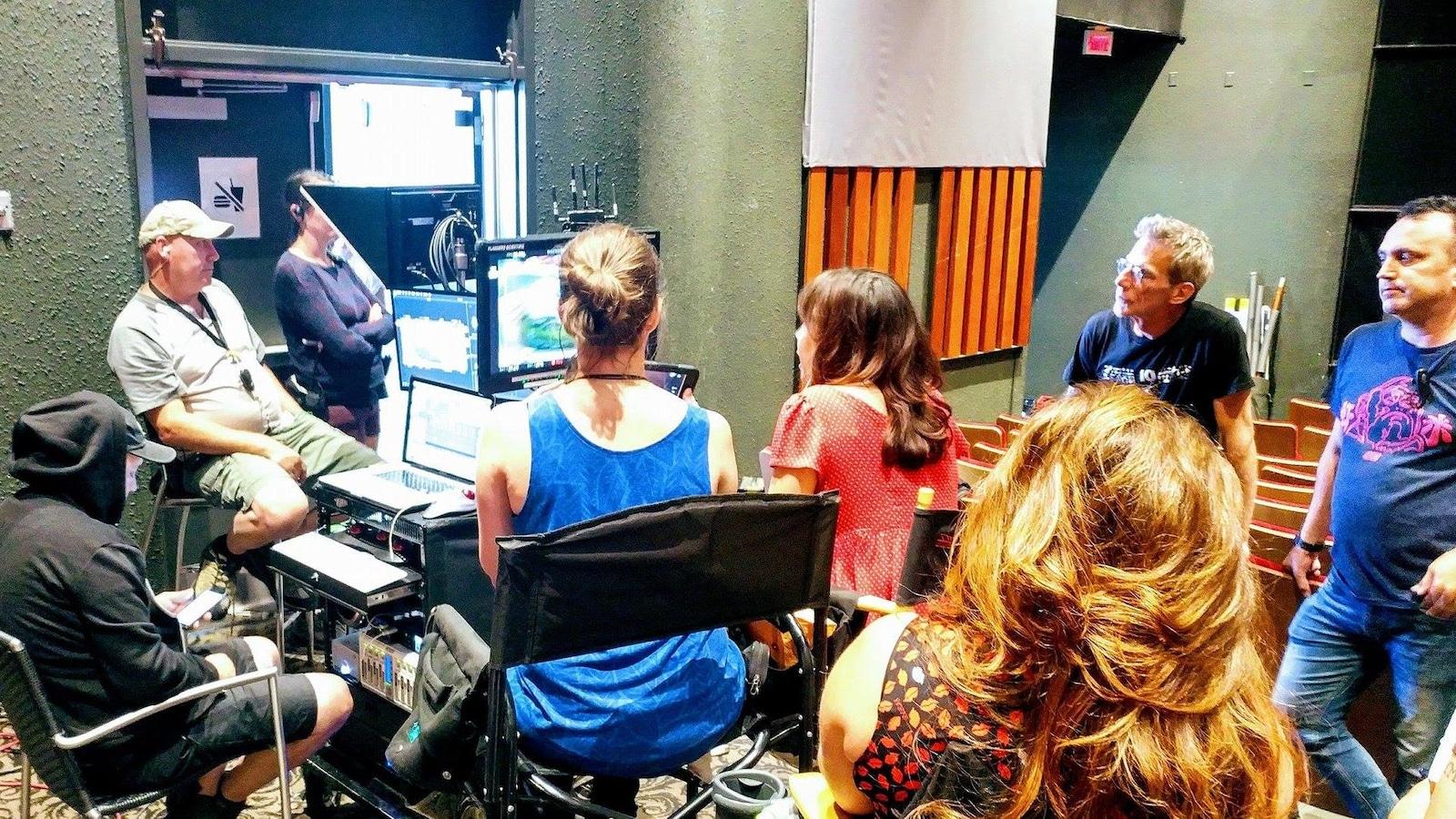 L'équipe de tournage analyse la scène et le jeu des acteurs, dans une pièce à côté