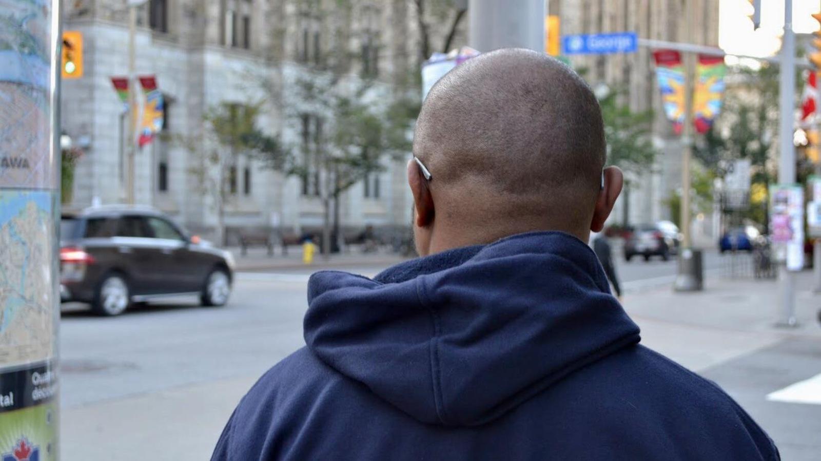 Un homme photographié de dos dans une rue