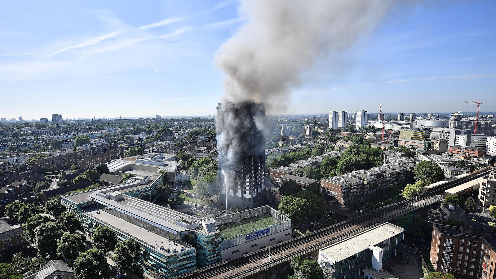 De la fumée s'échappe de cet immeuble résidentiel de 24 étages dans un quartier de l'ouest de Londres après que les flammes l'aient complètement ravagé.
