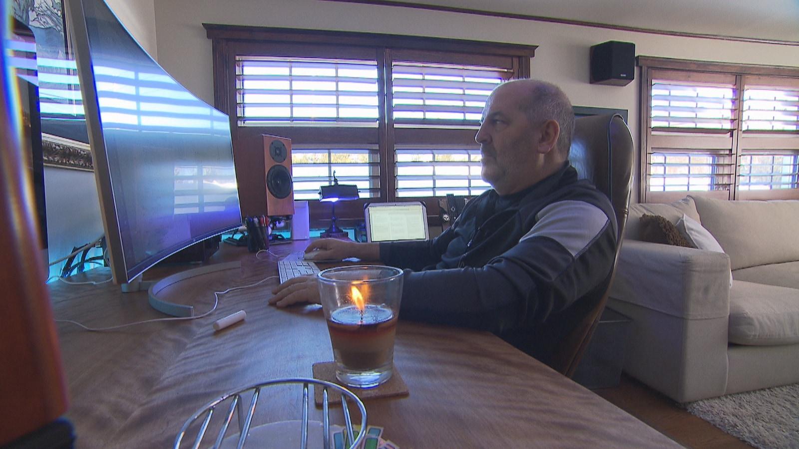 L'homme est assis devant son écran d'ordinateur.