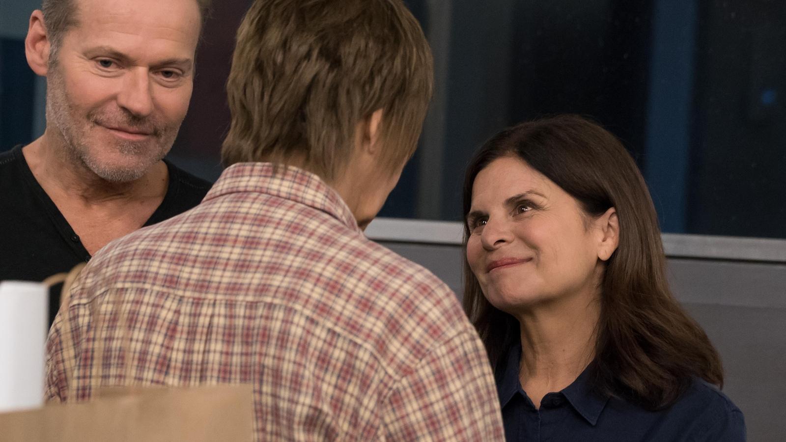 Deux personnes parlent avec une troisième personne, de dos.