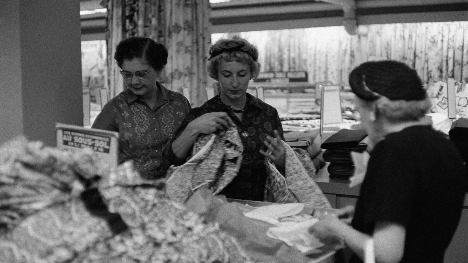 En noir et blanc, trois femmes manipulant des vêtements dans un rayon du magasin Dupuis Frères