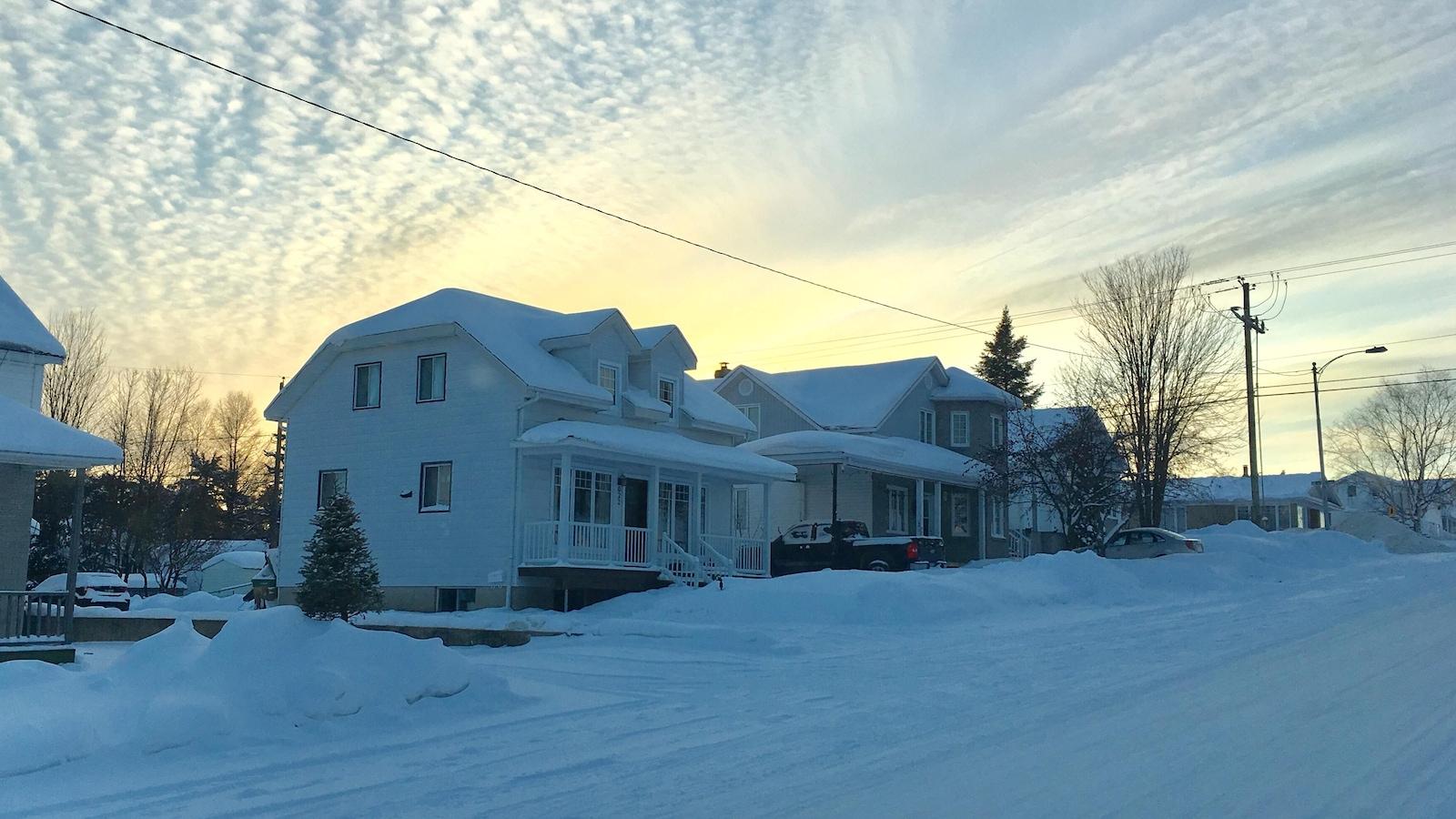 Une maison dans une rue enneigée.