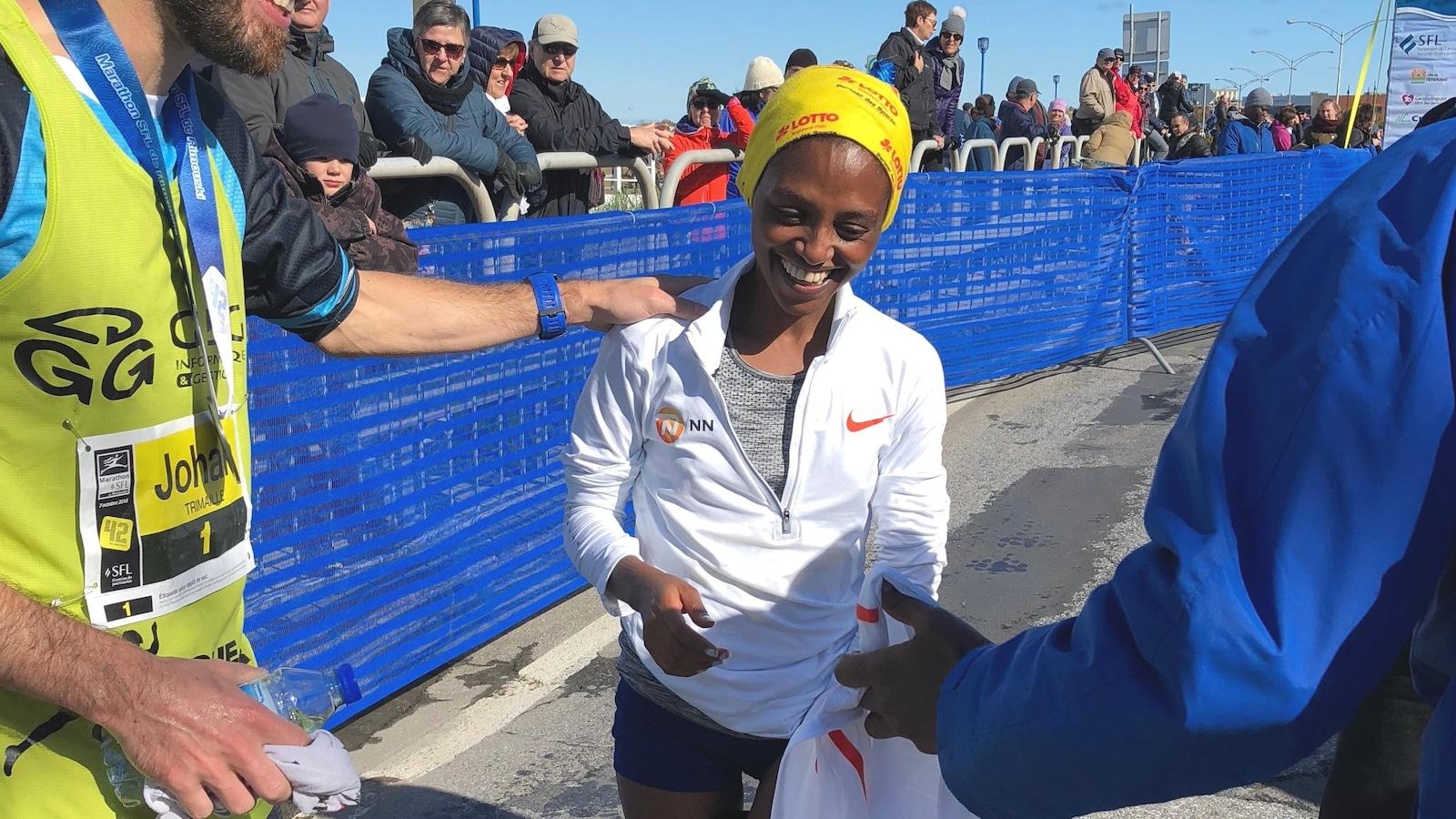 La gagnante, quelques instants après avoir franchi le fil d'arrivée, affiche un large sourire.