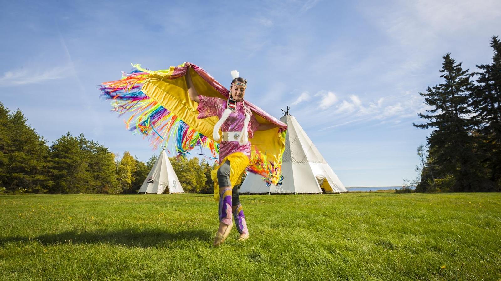 Une jeune femme autochtone danse en tenue traditionelle.