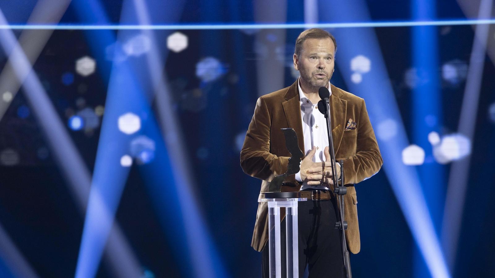 Un homme en veston brun fait ses remerciements devant un piédestal sur scène.