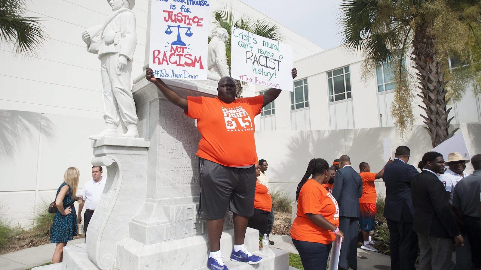 """Un homme brandit une pancarte sur laquelle on peut lire : """"Le palais de justice n'est pas pour le racisme."""""""