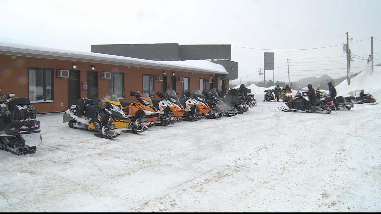 Des motoneigistes devant une partie du Motel Interprovincial à Pointe-à-la-Croix.