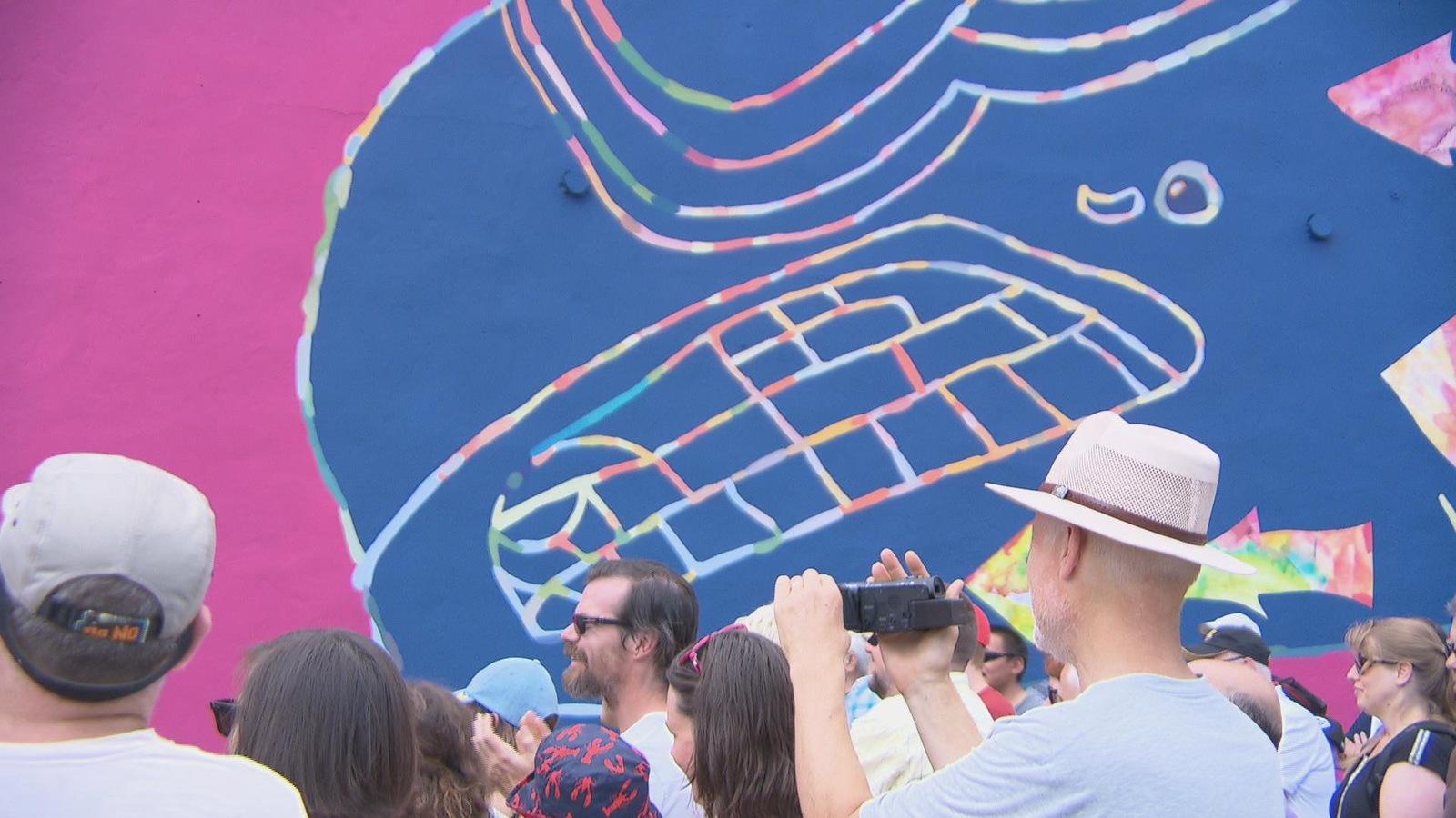 Des gens devant une murale