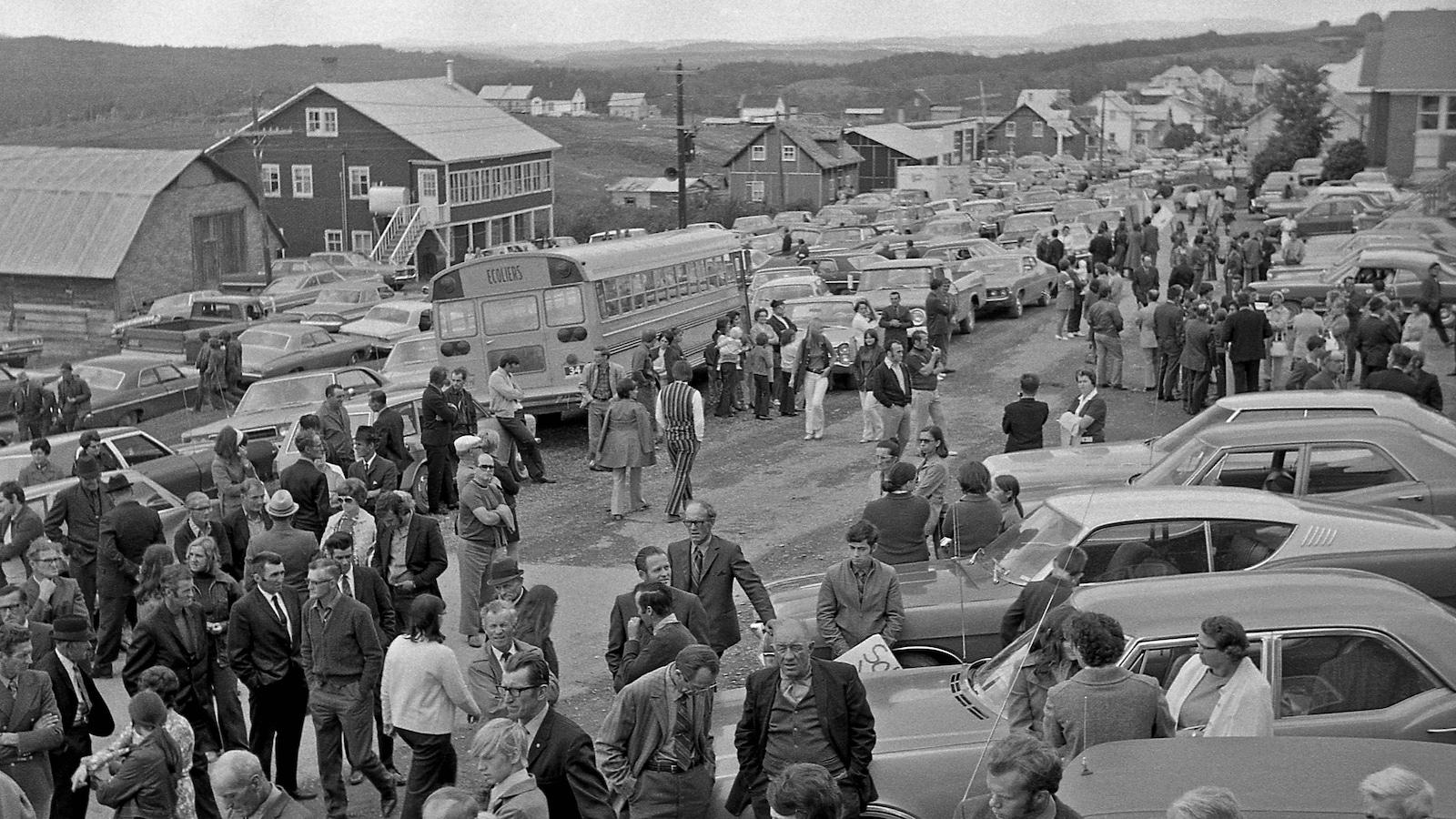 Une photo en noir et blanc de personnes qui sont dans une rue d'un village et se rassemblent. Des voitures sont stationnées à droite.