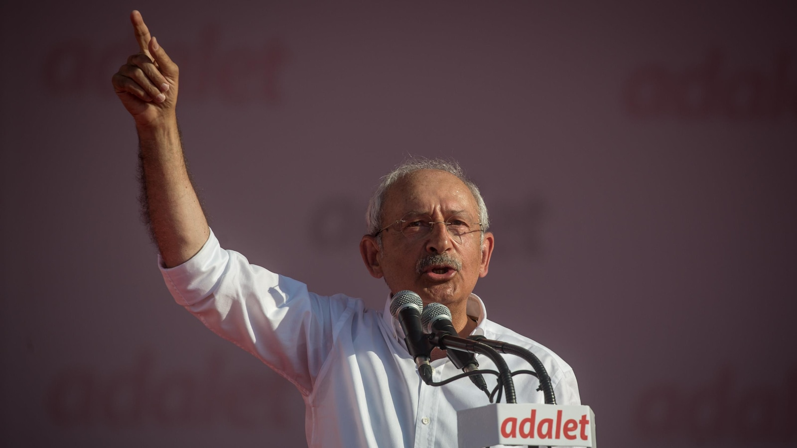 Kemal Kilicdaroglu livre un discours au micro, la main droit levée dans les airs.